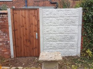 Concrete rock faced  fence panels fitted with T& G timber gate .